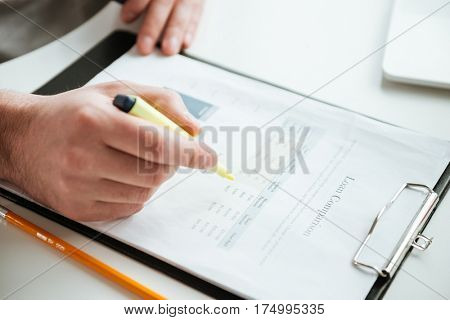 Cropped image of man which writing something on documents while sitting by the table