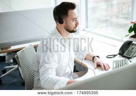 Side view of Man in white shirt and headset which sitting by the table and using computer