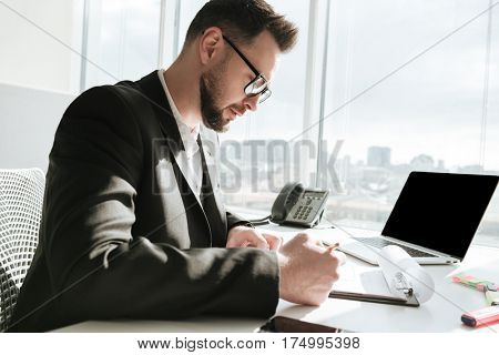 Side view of Business man in suit and eyeglasses which sitting by the table with laptop computer and writing something
