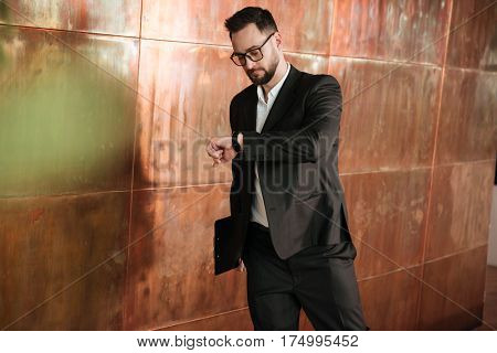 Business man in eyeglasses and suit which looking at wristwatch being in office
