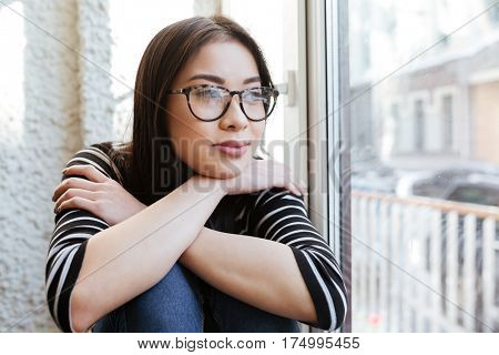 Thoughtful smiling Asian woman in sweater and eyeglasses which sitting on windowsill in cafeteria