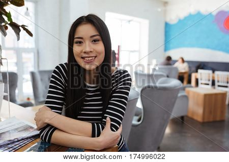 Smiling Asian woman in sweater which sitting by the table in cafeteria and looking at camera