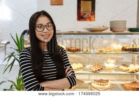 Asian woman in eyeglasses which standing with crossed arms near the counter on background