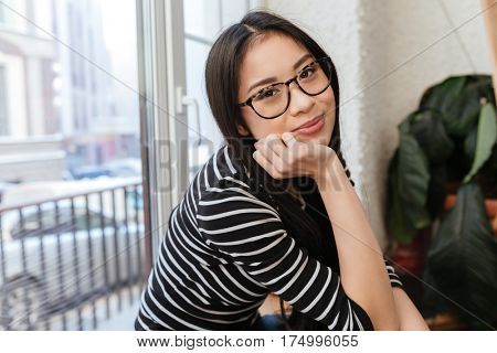 Side view of Young Asian woman in eyeglasses which sitting on windowsill in cafeteria and looking at camera