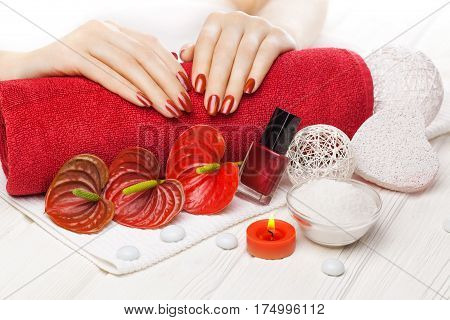 Luxury red manicure with oil and candles, red calla flower and towel on the white wooden table.