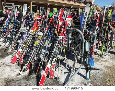Stratton VT March 05 2017: Skis and snowboards are resting on the racks near the main lodge at Stratton Mountain.