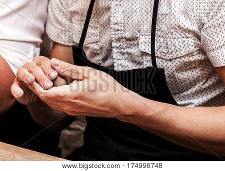 man sculpts with clay in pottery place