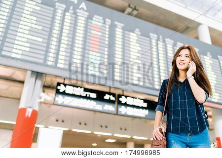 Beautiful Asian woman traveler on mobile phone call at flight information board in airport holiday vacation travel or communication concept