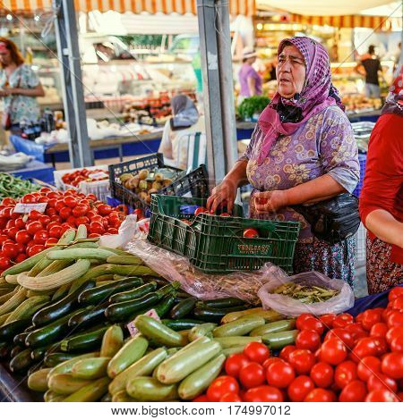 KEMER/ TURKEY - AUGUST 31, 2015. Aged woman selling the vegetables in the Turkish market. Kemer, Turkey.