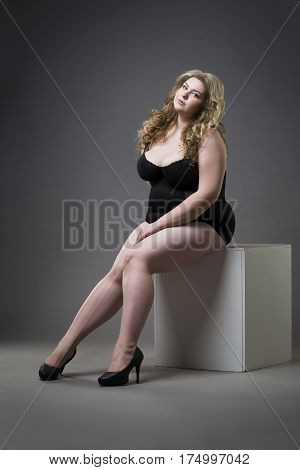 Young beautiful blonde plus size model in shapewear xxl woman in slimming underwear on gray studio background full length portrait