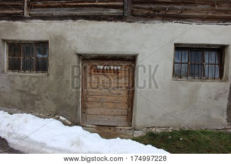 Old grey barn facade with crafted door and grated windows in mountain area. Basement of traditional old barn with closed entrance door and windows and snow in front.