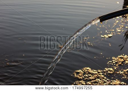 Water running from tube into lake reservoir. Water stream from outdoor tap on the lake bank.