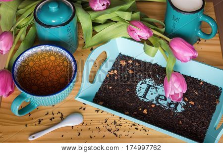 A cup of tea and a bouquet of tulips. Two cups for sugar and milk. A tray with the inscription Tea. On a tray of dry tea