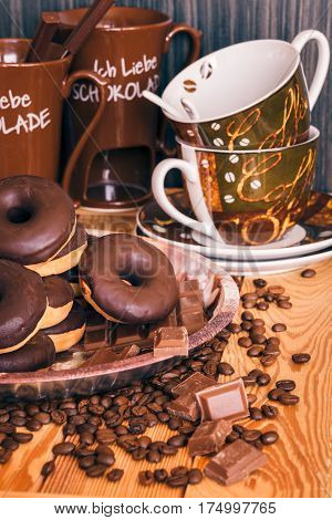 I love chocolate. A tray with donuts and chocolates. A delicious chocolate dessert. Cups for coffee and fondue. The coffee is scattered on the table