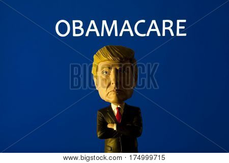 Donald Trump Caricature Bobble Head standing in front of a sign reading Obamacare - also known as the Affordable Healthcare Act