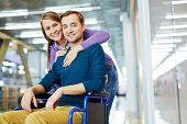Portrait of young happy couple: pretty girl hugging her smiling handicapped boyfriend in wheelchair poster
