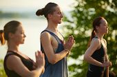 Close-up view of three friends holding hands in namaste while meditating outdoors poster