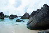 Natural black rock formation on the seashore at the beach in Belitung Island at daytime, Indonesia. poster