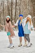 Three smiling women skate at outdoor skate rink in winter park. poster