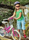 Bicycle children with ladies bikes in summer park. Child road bike for running on nature. Kid girl in helmet cycling fording throught water . Cycling trip is good for health outdoor. poster