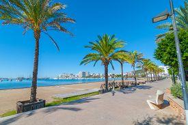 Ibiza sun shines of the beach in Sant Antoni de Portmany,  Take a walk along main boardwalk or in the sand.   November beach in warm morning sunshine.