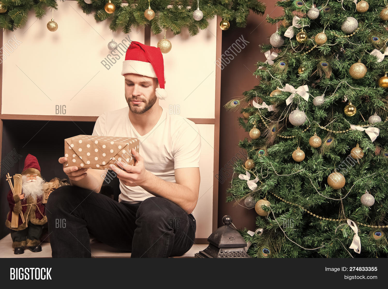 265b31ec86973 Macho in red hat with wrapped boxes at fireplace. Man santa with presents  at xmas tree. Christmas