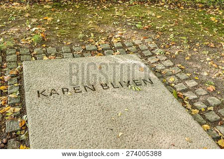The Headstone Of The Famous Danish Writer Karen Blixen, With Yellow Autumn-leaves.  The Tomb Is In T