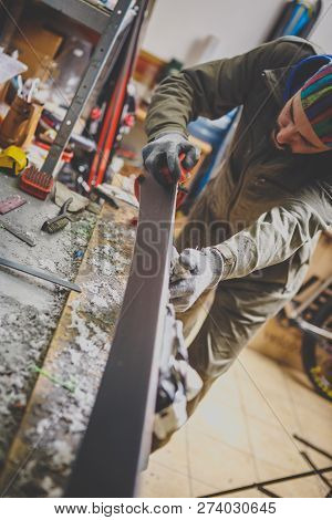 Male Worker Repairing Stone, Edge Sharpening In Ski Service Workshop, Sliding Surface Of The Skis. S