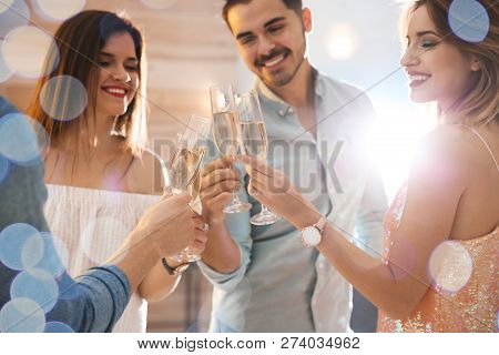 Friends Clinking Glasses With Champagne At Party Indoors