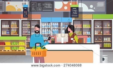 Retail Woman Cashier At Checkout Supermarket Man Customer Holding Basket Food Paying Smartphone Shop