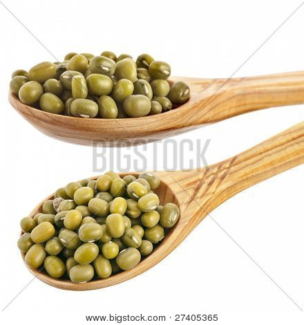 green soja mung beans over the wooden spoon isolated on white