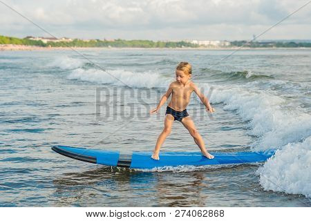 Little Boy Surfing On Tropical Beach. Child On Surf Board On Ocean Wave. Active Water Sports For Kid