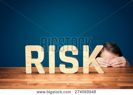 Risk Manager Has A Fear Of The Risk In Business. Worried Or Timid Businessman Is Hiding Behind The T