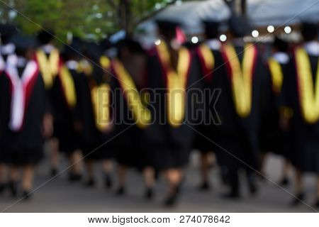 Blurr Image Of A Group Of Graudates On Black Gown Walking On The Street