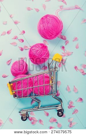Bright Pink Wool Balls. Shopping Cart Full Of Yarn. Soft Cotton Wool Balls And Pink Petals. Flat Lay