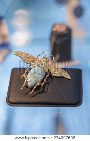 Precious brooch in the form of a beetle on a shop window. Antic brooch. golden brooch in the form of a beetle poster