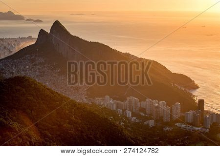 Two Brothers Mountain Silhouette By Sunrise, With Apartment Buildings At The Bottom And Favela Rocin