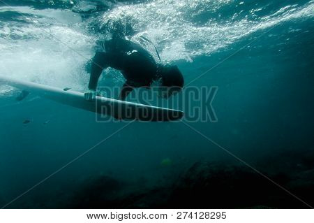 Man In The Black Swimsuit Flowing Down Holding A White Surf Board Dive Under The Wave Of A Clear Blu