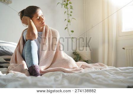 Beautiful peaceful brunette relaxing in sunlight on bed
