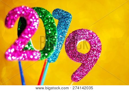 closeup of some glitter numbers of different colors forming the number 2019, as the new year, on a bright yellow background