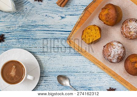 Six Orange Pumpkin Muffins On Cutting Board Covered With Baking Paper, One Is Bitten Off In Right Si