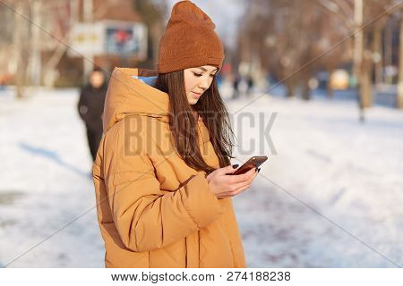 Sideways Shot Of Female Youngster Dressed In Stylish Hat And Loose Jacket, Holds Mobile Phone, Surfe