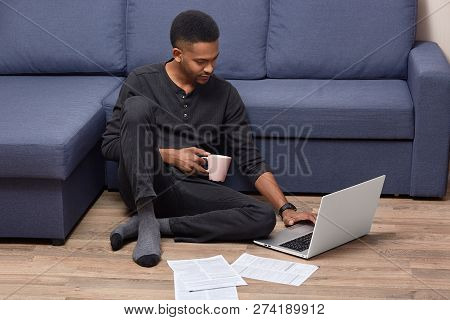 Dark Skinned Young Male Adult Does Paper Work At Home, Studies Documents, Holds Mug With Hot Beverag
