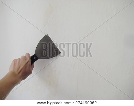 Women Hand Holding Putty Knife Patching A Hole In White Wall. Renovation And Repair Process Indoors,