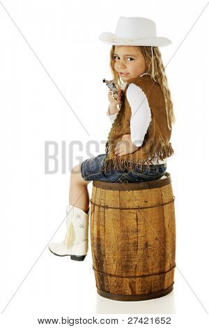A cute cowgirl kindergartner, twisting on her barrel-seat to shoot at the viewer.  On a white background.