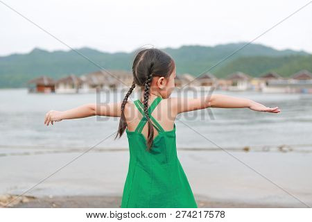 Little Asian Child Girl Stretch Arms And Relaxes In Hillside At Morning
