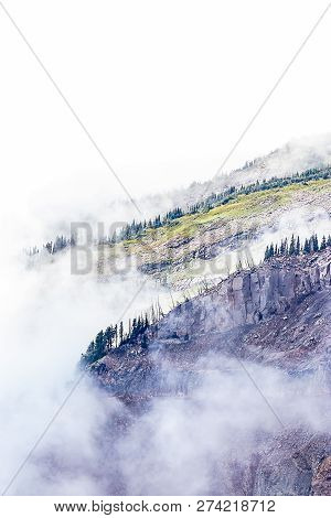 Huge Harsh Purple Mountainrange With Green Trees And Clouds Cover