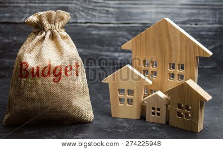 Bag With Money And The Inscription Budget And Wooden Houses. The Concept Of The City Budget. Financi