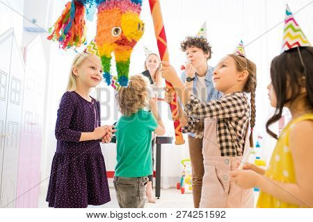Content Confident Girl In Party Hat Standing At Colorful Horse Pinata And Hitting Cit With Bat At Ki