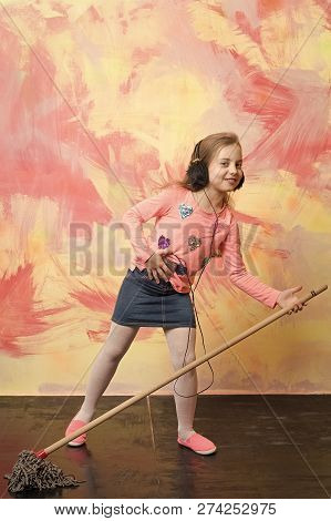 poster of Child cleaner with broom on colorful background. Housekeeper kid in earphones. Cleanup and order services. Small girl listen music with mop. Cleaning and purity.